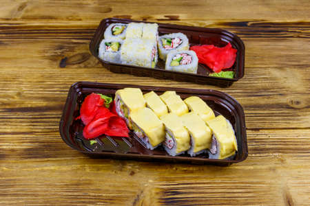 Set of sushi rolls in plastic boxes on wooden table. Sushi for take away or delivery of sushi in plastic containers