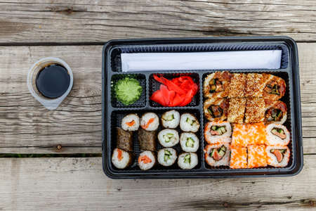 Set of sushi rolls in plastic box on wooden table. Sushi for take away or delivery of sushi in plastic container. Top view