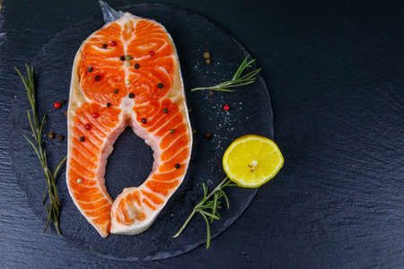 Raw salmon steak with spices on black slate. Top view 写真素材