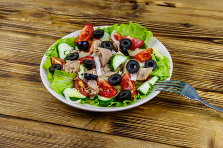 Tasty tuna salad with lettuce, black olives and fresh vegetables on wooden table 写真素材