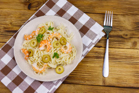 Spaghetti pasta with prawns, green olives and parsley on wooden table. Top view