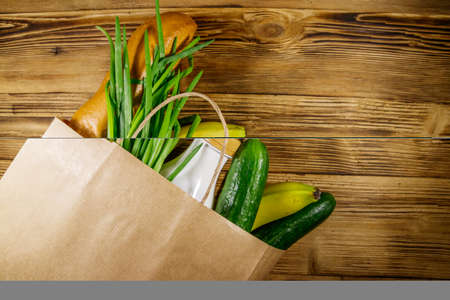 Paper bag with different food on wooden table. Top view. Grocery shopping concept