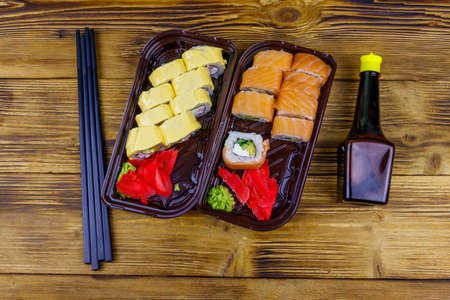 Set of sushi rolls in plastic boxes, soy sauce and chopsticks on wooden table. Top view. Sushi for take away or delivery of sushi in plastic containers