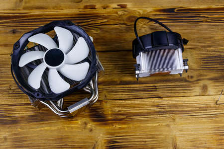 Two modern CPU coolers on a wooden desk. Top view