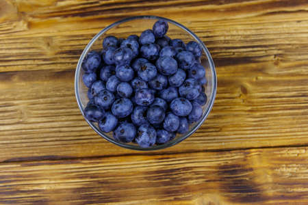 Fresh blueberry in glass bowl on a wooden table. Top view