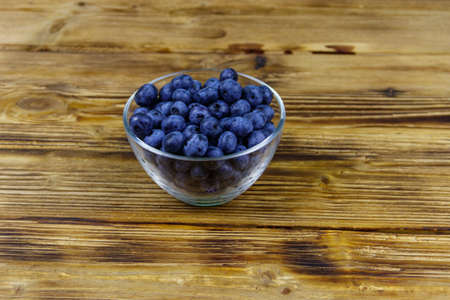 Fresh blueberry in glass bowl on a wooden table