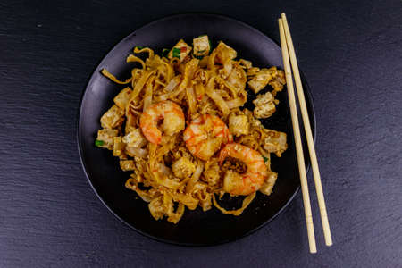 Stir-fried rice noodles Pad Thai with prawns and tofu in a plate on black slate background. Top view. Thai food