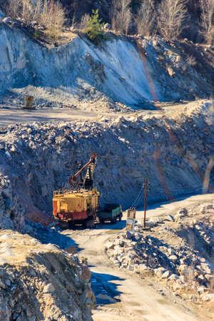 Big yellow excavator working in a granite quarry