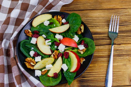 Autumn spinach salad with apple, feta cheese, walnut and dried cranberry on wooden table. Top view. Healthy vegetarian food