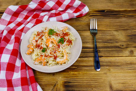 Spaghetti pasta with prawns, tomato sauce and parsley on wooden table