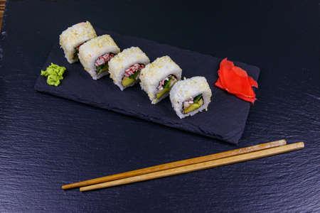 Uramaki sushi rolls with surimi on a black slate 写真素材
