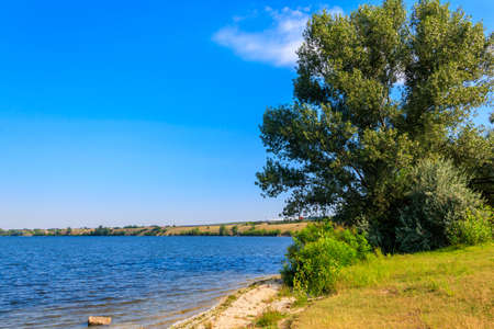 Summer landscape with beautiful river, green trees and blue sky 写真素材