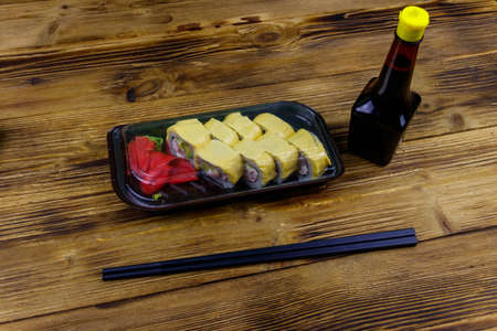 Sushi cheese rolls in plastic box on wooden table. Sushi for take away or delivery of sushi in plastic container 写真素材
