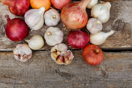 Fresh garlic and onion on a rustic wooden table. Top view