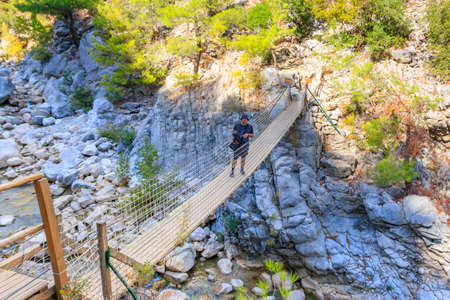Young man standing on suspension wooden bridge in Goynuk canyon in Antalya province, Turkey Фото со стока