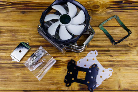 Modern CPU cooler with installation kit on a wooden desk. Top view