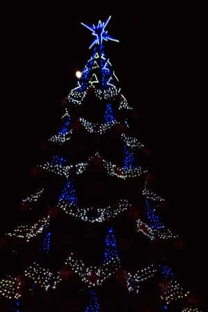 Decorated Christmas tree with multi-colored lights at night 版權商用圖片 - 159614944