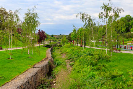 Beautiful view of the city park with arched footbridge across small river and young trees
