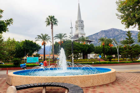 Kemer, Turkey - October 21, 2020: White clock tower and fountain in the center of Kemer, Antalya province, Turkey Editorial