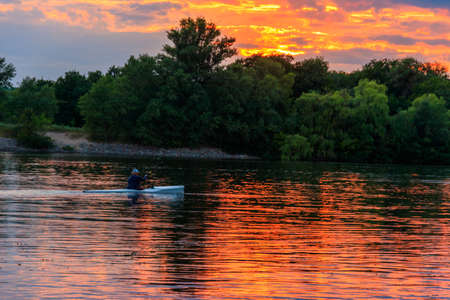 Man kayaking along the Dnieper river at sunset