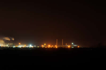 Night view of industrial district of the city and smoke pipes of factory