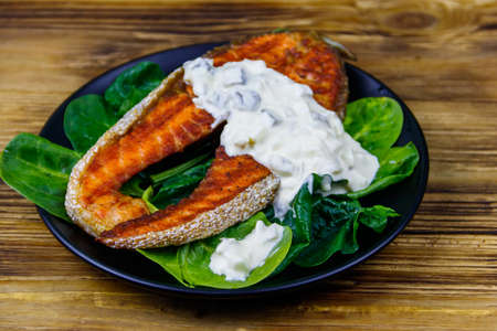 Grilled salmon steak with spinach and tartare sauce on wooden table