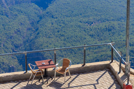 Table and chairs on a viewing platform for rest on a top of Tahtali mountain near Kemer, Antalya province in Turkey