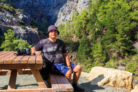 Young man sitting at wooden table in Goynuk canyon in Antalya province, Turkey