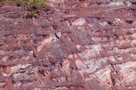 Close-up of red mining levels at iron ore quarry. Open-cast mine, open pit. Background, texture
