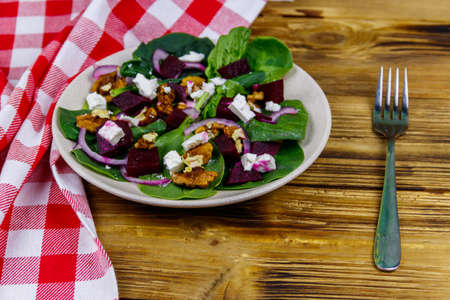 Tasty spinach salad with boiled beetroot, feta cheese, walnut and red onion on wooden table. Healthy vegetarian food 写真素材