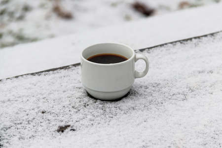 Cup of coffee on a snow covered table at winter