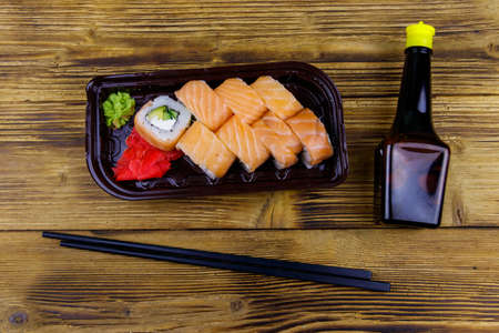 Sushi rolls Philadelphia in plastic box on wooden table. Top view. Sushi for take away or delivery of sushi in plastic container 写真素材