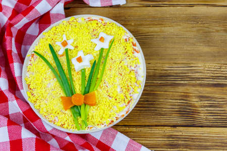 Traditional russian layered salad Mimosa with spring decoration Daffodil on wooden table. Top view. Decoration is made of egg, green onion and carrot