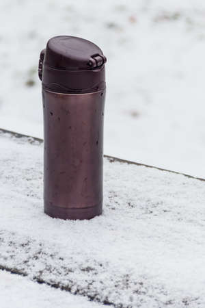 Thermo mug on a snow covered table at winter