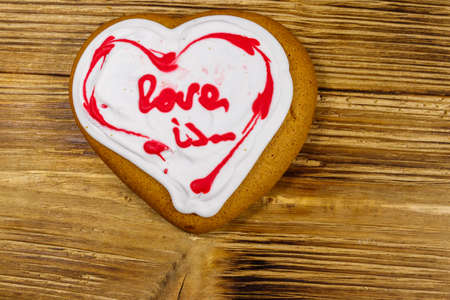 Heart shaped gingerbread cookie on wooden table. Top view. Dessert for valentine day Banque d'images
