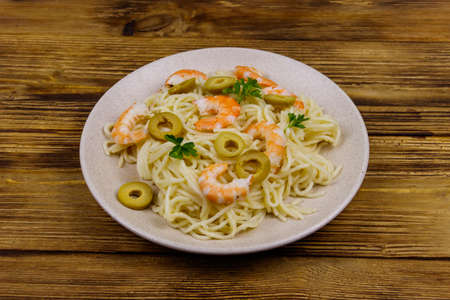 Spaghetti pasta with prawns, green olives and parsley on wooden table Banque d'images