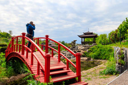 Travel photographer man with professional camera taking photos of Japanese garden