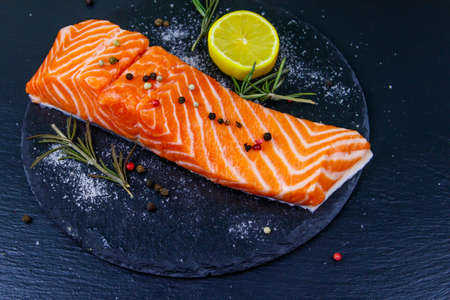 Raw salmon fillet with spices on black slate