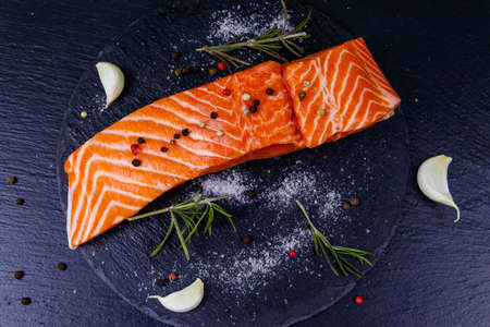 Raw salmon fillet with spices on black slate. Top view Stok Fotoğraf