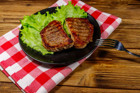 Grilled pork steaks with lettuce leaves on wooden table Stok Fotoğraf