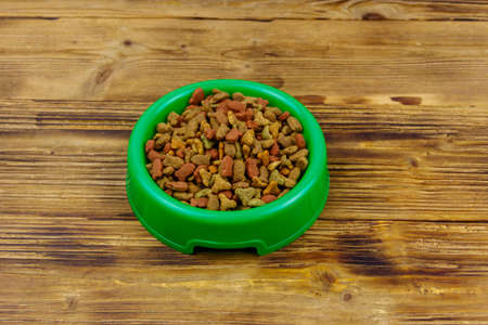 Dry food for cat or dog in bowl on wooden background. Pet food on wood surface