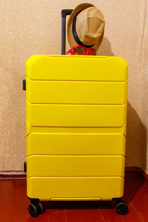 Yellow suitcase with sunglasses and hat in a room. Travel concept
