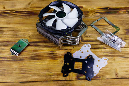 Modern CPU cooler with installation kit on a wooden desk