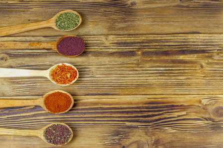 Set of different aromatic spices on wooden table. Top view, copy space