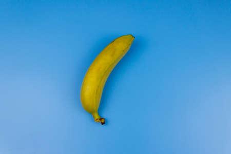 Yellow banana on pastel blue background. Top view, flat lay, minimal design