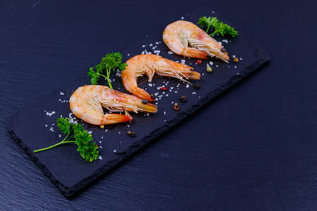 Big raw red prawns with parsley, salt and pepper on a slate board on black background