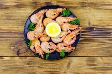 Red boiled prawns with lemon and parsley on wooden table. Top view