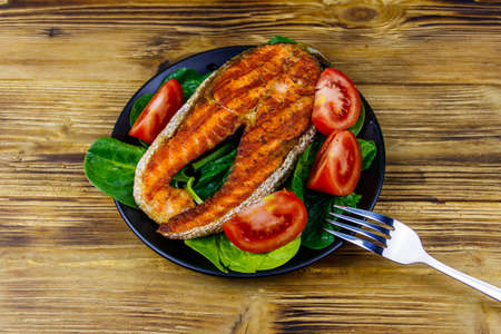 Grilled salmon steak with spinach and tomatoes on wooden table. Top view
