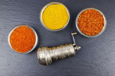 Set of different aromatic spices and spice mill on black slate. Top view Archivio Fotografico