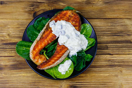 Grilled salmon steak with spinach and tartare sauce on wooden table. Top view Archivio Fotografico